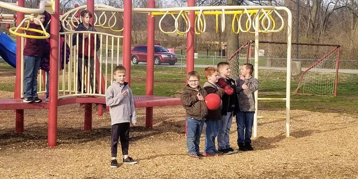 Young students stop playing to cover their hearts for the National Anthem